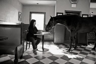 A woman and horse facing each other at a table in an empty diner.